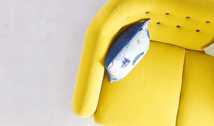 Yellow Couch with Blue Pillow - Buildout Pros
