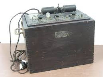 "Advanced Oscilloclast - A larger, more cubical box with hinged lid. Three rotary Rate switches and electrical ""pulse"" generator on top panel, indicator light bulb, and connections for cables."