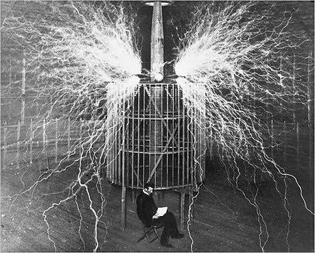 Tesla sitting in front of one of his coils at the Wardenclyffe lab