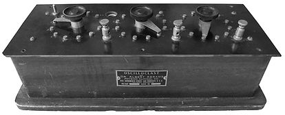 The original Oscilloclast appeared as a long rectangular black box with three rotary Rate switches, switch button, light bulb, and four binding terminal posts.