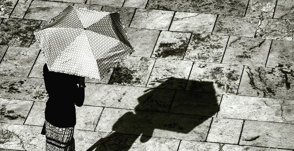 Une femme qui marche se protège avec une ombrelle