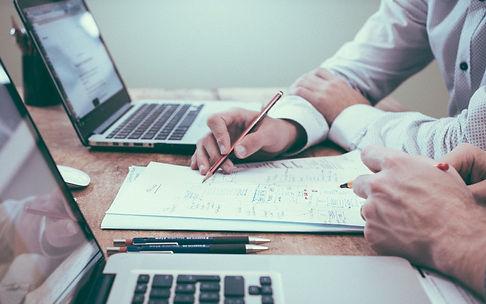 2 hommes travailllent ensemble sur un papier à établir un bilan patrimonial