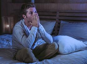 despairing man sat on a bed