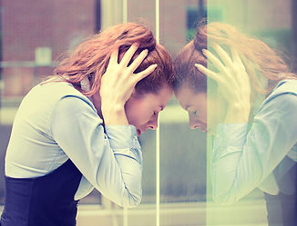 stressed woman resting her head on a window