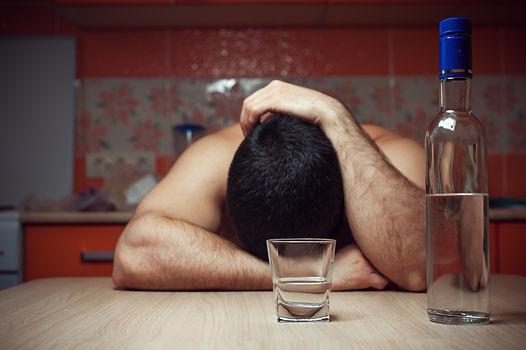 Alcohol addicted man sleeping at the tab