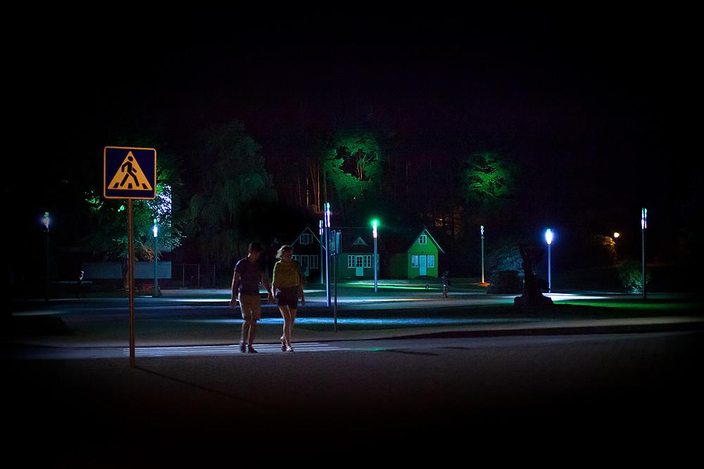 Kaksi ihmistä kävelee yöllä kylässä, jonka katuvaloja valaisevat eriväriset lamput.