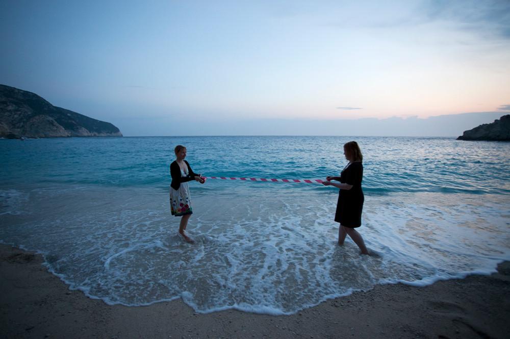 Kaksi henkilö seisoo rannalla, aivan vedenrajan tuntumassa.