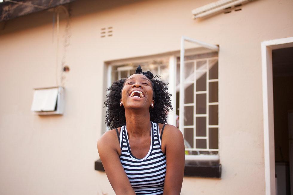 Nainen nauraa ikkunan edessä