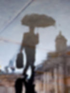 Thrive Future, Management Consultant, reflection in pavement, man with umbrella, wet city street