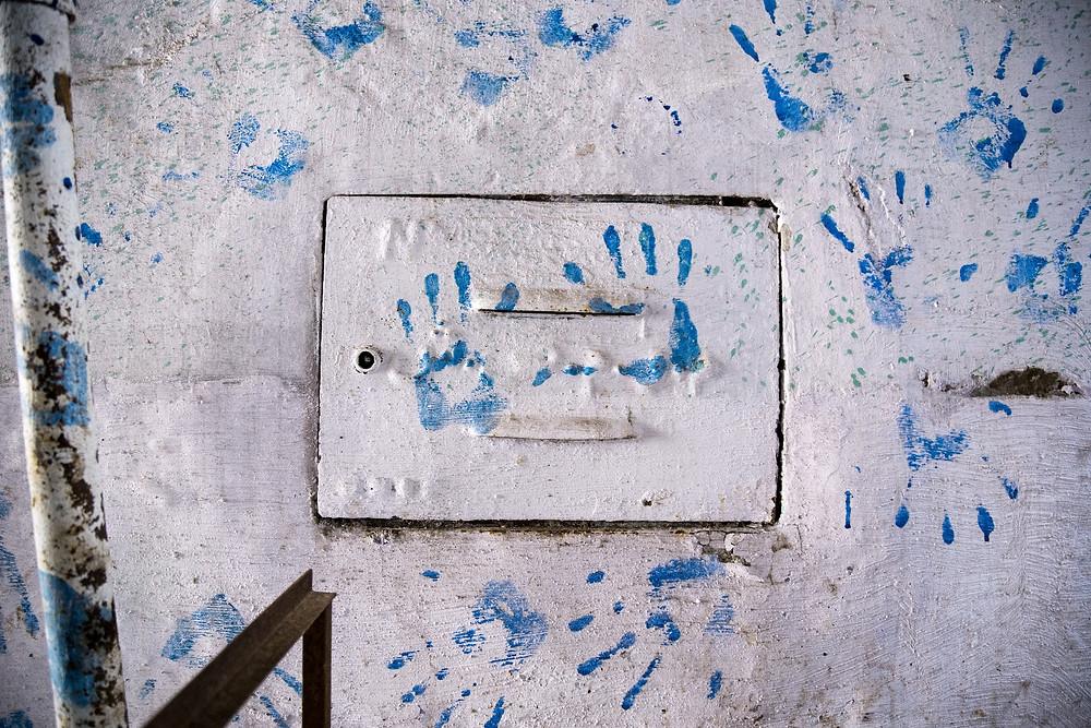 Blue handprints on a wall