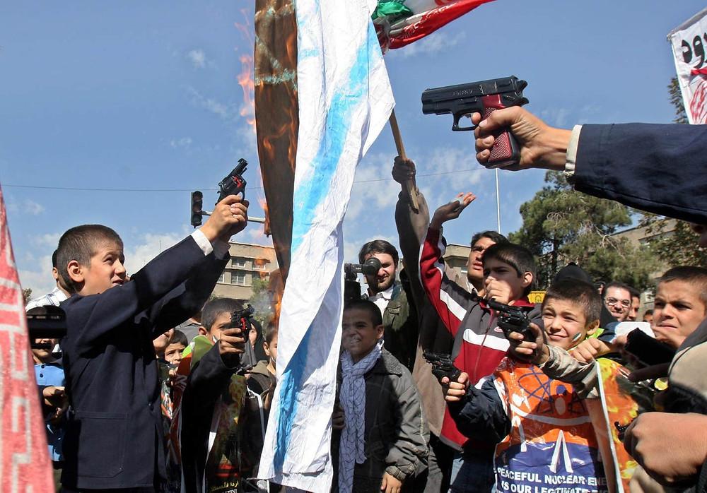 "Iranian schoolboys shooting toy guns at an Israeli flag as it burns during an anti-Israeli rally marking ""Al-Quds Day"" (Jerusalem Day)"