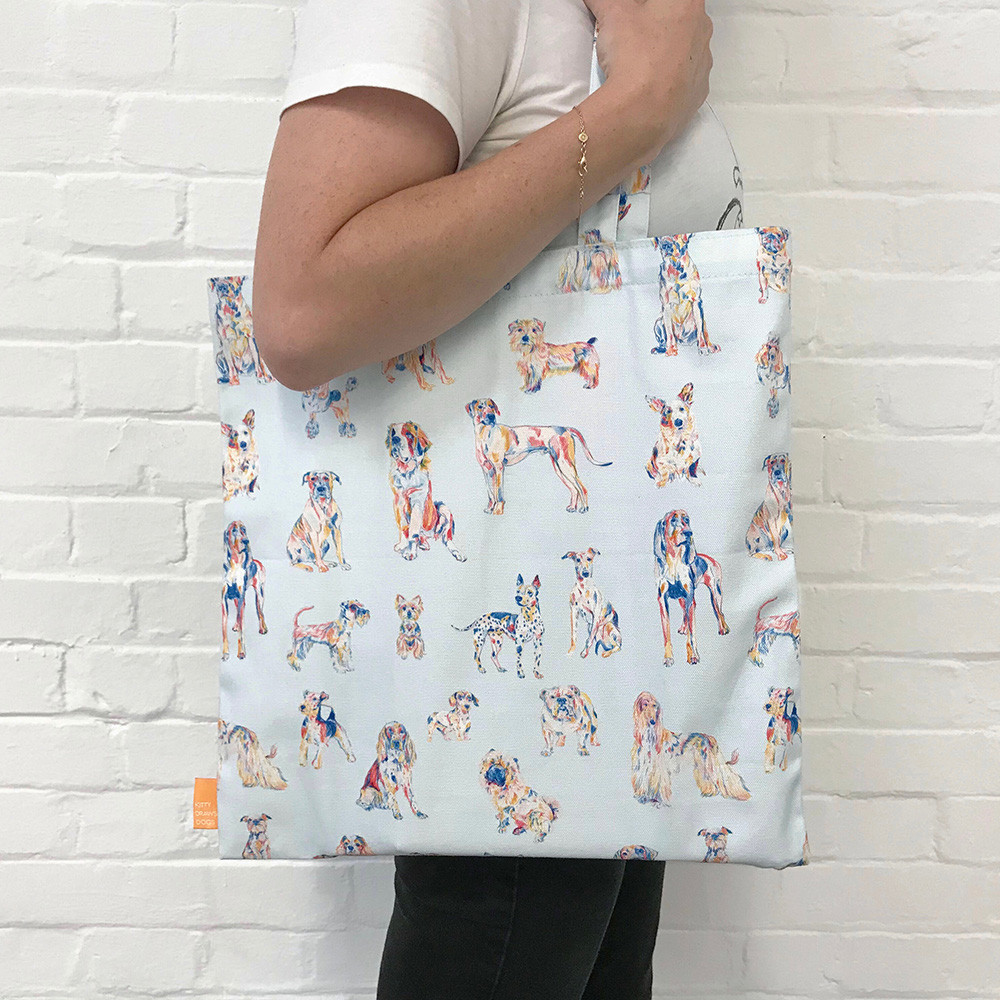 Light blue tote bag with colourful dog drawings.