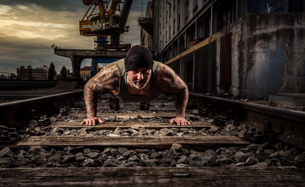 Strongman Timo mit Pushup / Liegestütze auf verlassenen Gleisen Basler Rheinhafen