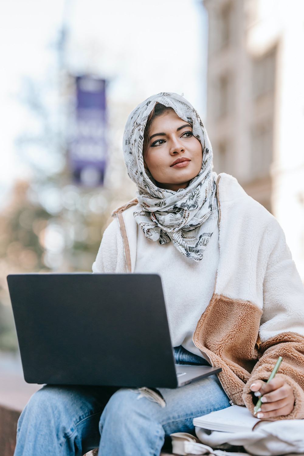 A hijab wearing woman sitting outside and working on her laptop