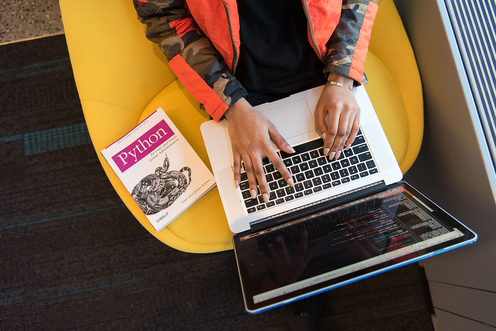 """Woman coding on her laptop with a book titled """"Python"""" next to her"""