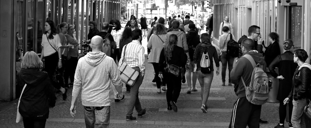 Image of people walking on a busy street in black in white (probably somewhere in North America)