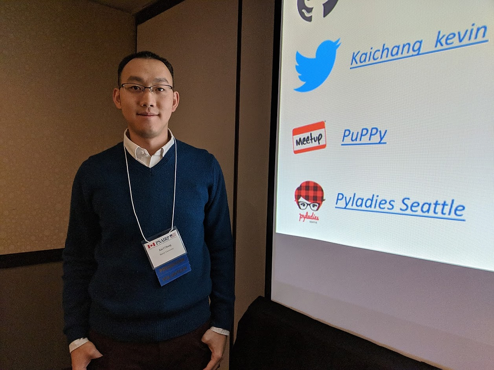 """Kai """"Kevin"""" Chang at a presentation standing next to a powerpoint presentation"""