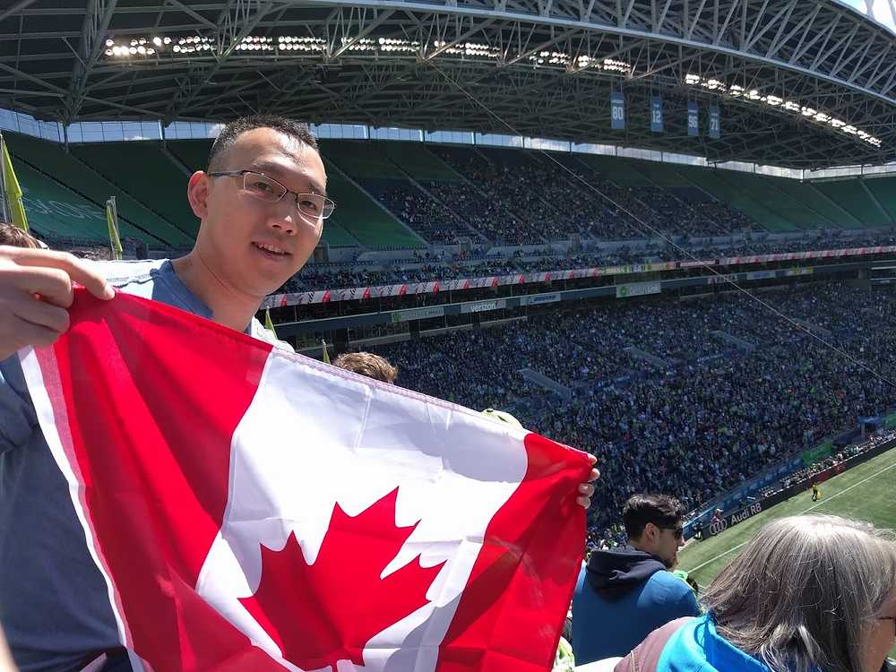 """Kai """"Kevin"""" Chang at a sports game holding a Canadian flag"""