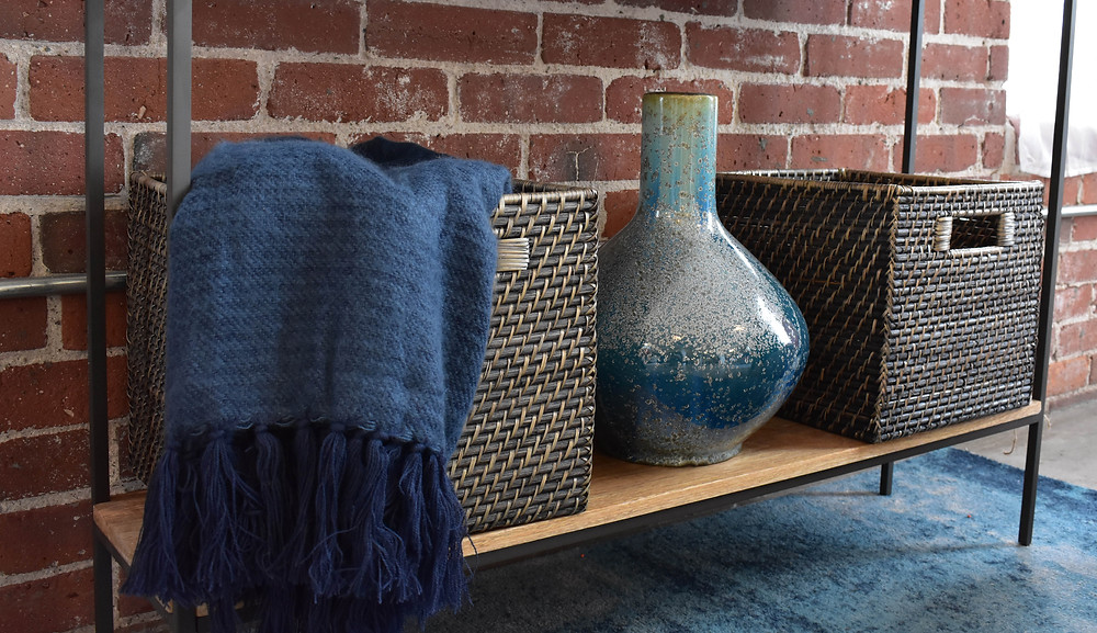 Cozy blue throw with woven storage baskets and a blue vase