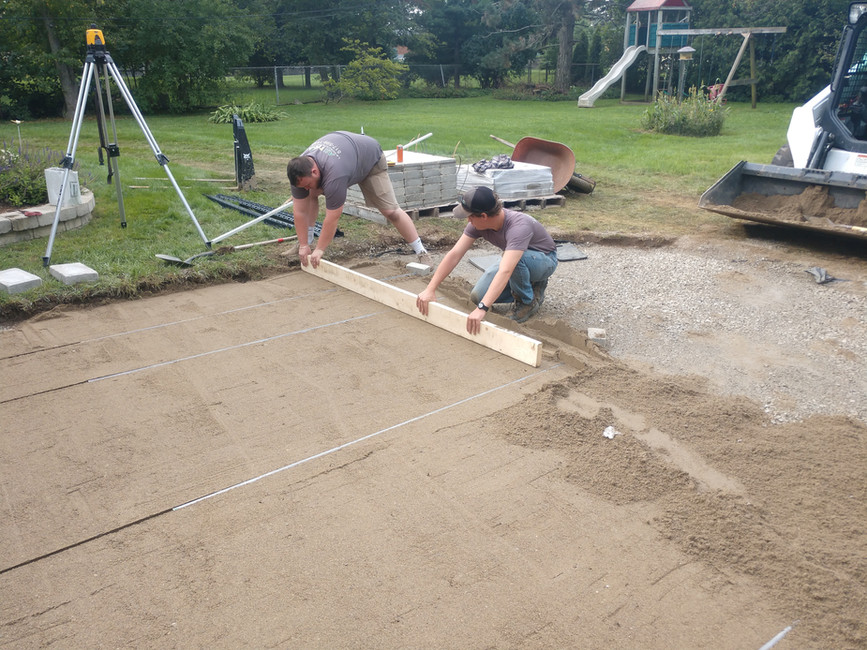 Leveling The Sand Before Laying The Brick Paver Patio