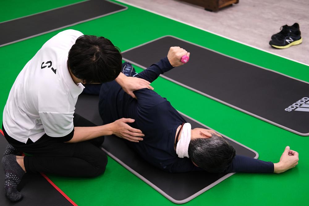 メディカルフィットネス SINKA GYM で行われている肩関節周囲炎を改善するためのトレーニングの風景です。こちらの方は長年の姿勢の乱れが原因で肩の痛みが発生してしまっていたようです。歩行分析でも重心の乱れが確認できました。肩関節周囲の筋力バランスを整え、症状の改善を試みます。