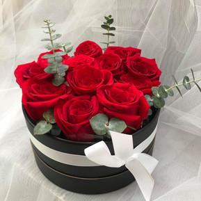 A dozen red roses in black round box