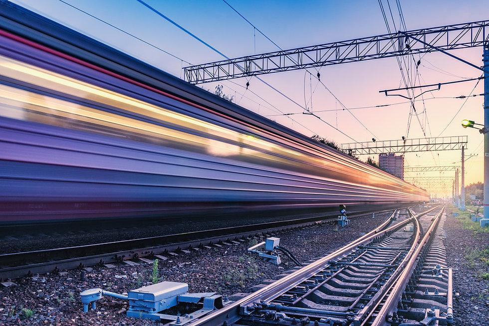 Passenger train moves fast at sunset tim