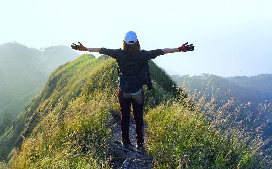 אישה פורסת ידיים על ההר