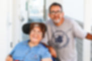 Woman in a wheelchair smiling with her husband