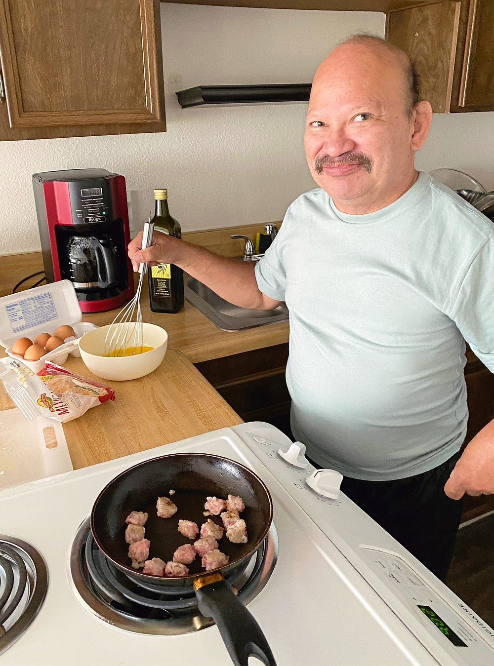 David cooking breakfast in his new home