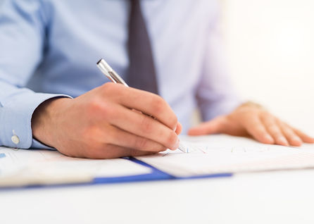 Businessman writing in a document. Focus