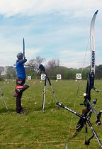 Archer on the shooting line with a recurve bow in the foreground