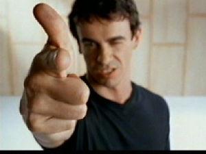 Roberto Rocha apontando dedo para câmera na campanha de desarmamento.