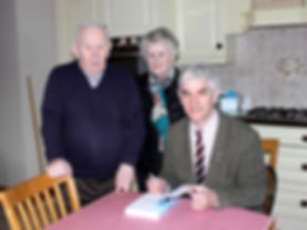 """Clive Hathaway Travis presenting copy of Looking for Prince Charle's Dog to """"hooded man"""" Paddy-Joe McClean and wife Annie"""
