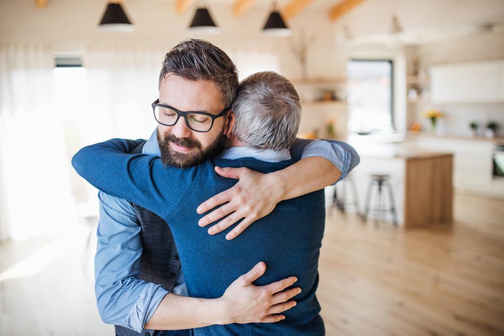 Hijo adulto abrazando a padre anciano