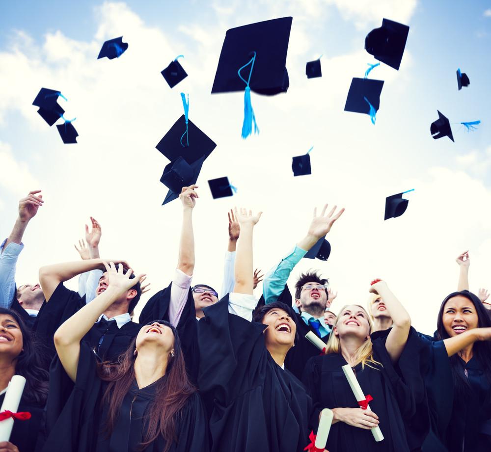 Graduates throw mortar boards into air in celebration