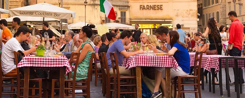 Pessoas em mesas ao ar livre na Itália