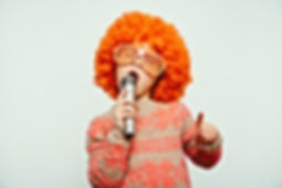 girl in a wig and sunglasses singing int