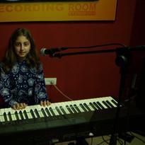 תלמידת בית הספר למוסיקה לומדת לנגן ולשיר