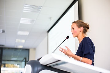 Image of a female presenter at the podium.
