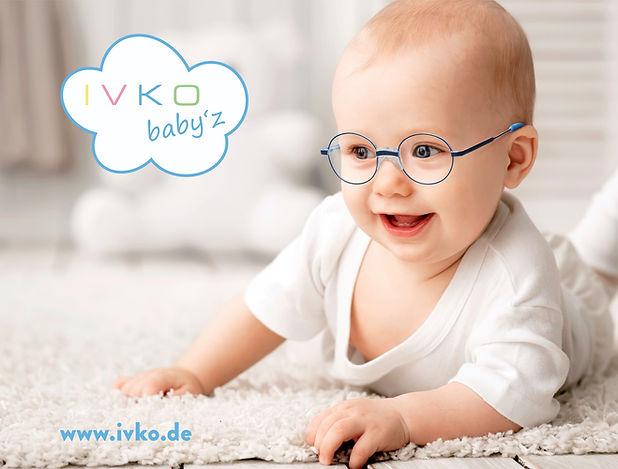 Baby mit Brille auf einem Teppich IVKO Baby