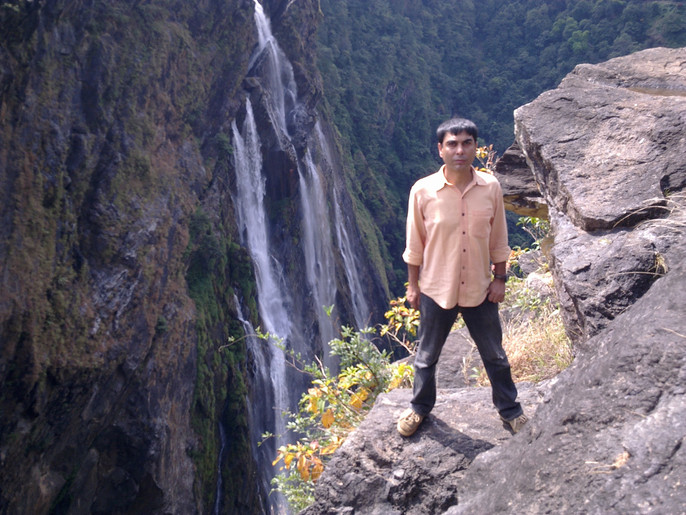 Man standing at a cliff with waterfall