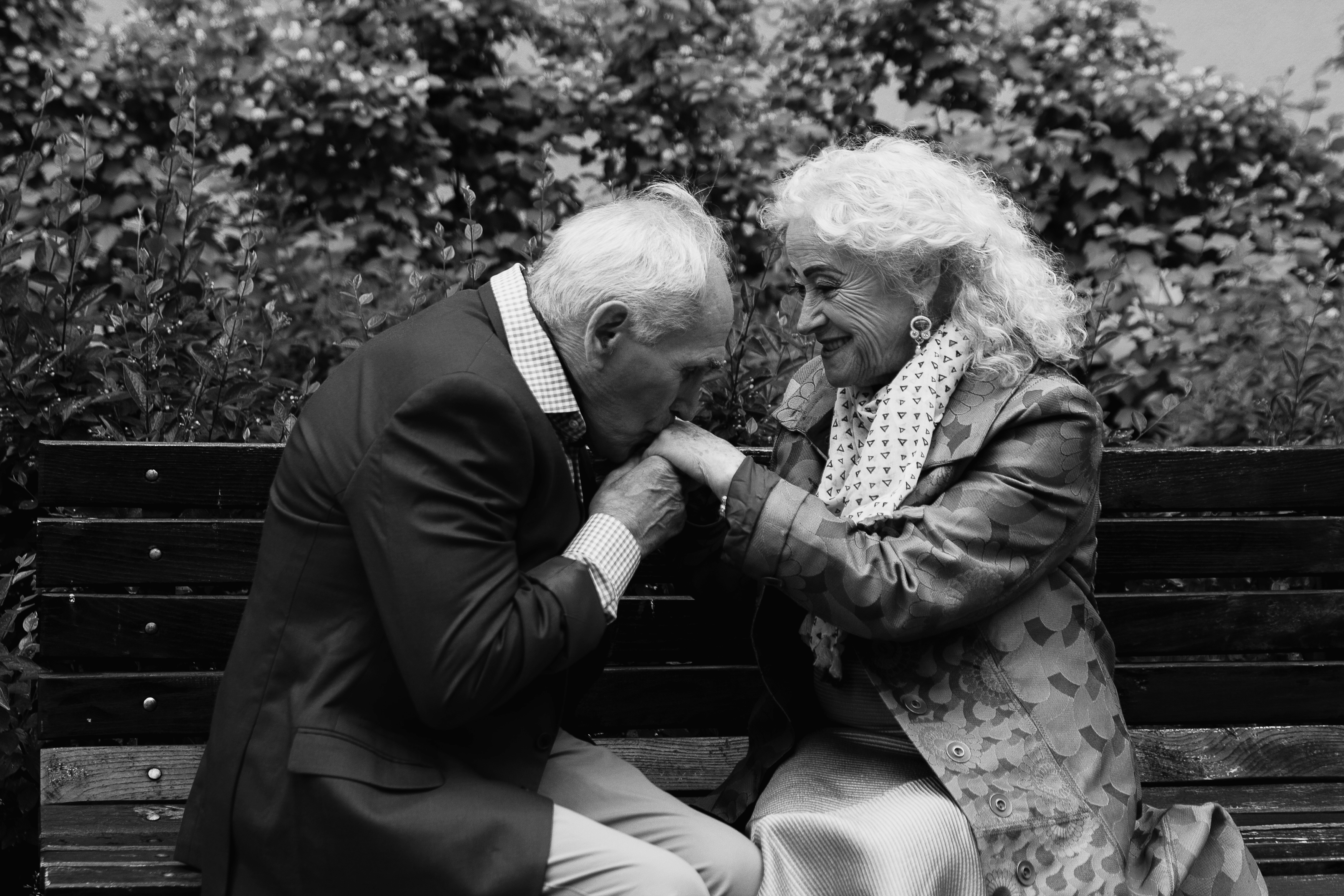 Elderly couple sitting on a bench outdoo