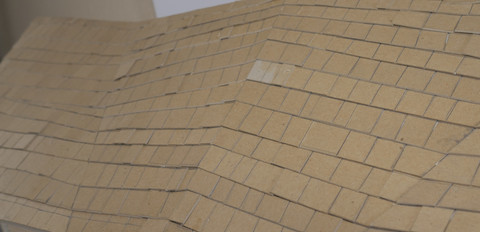Close up of roof. Shingles cut individually from chipboard. Laying on a sheet of illustration board with wood framing.