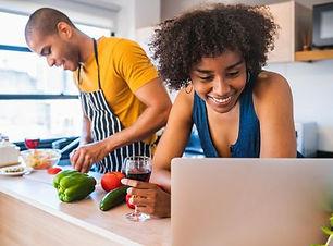 woman-using-laptop-while-man-preparing-f