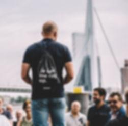 Around 010 gids Wesley van den Bos laat een groep Rotterdam zien bij de Erasmusbrug