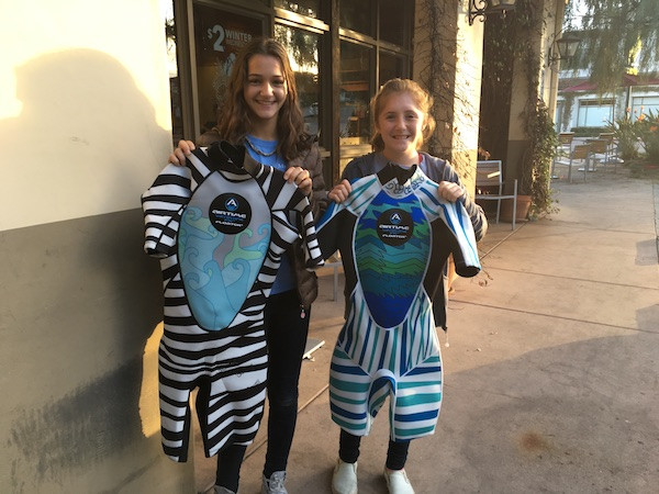 Jenna and Sadie, two of the Airtime Watertime design contest winners, show the wetsuits made from their original design