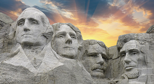 Image of Mount Rushmore with sun rays and clouds.
