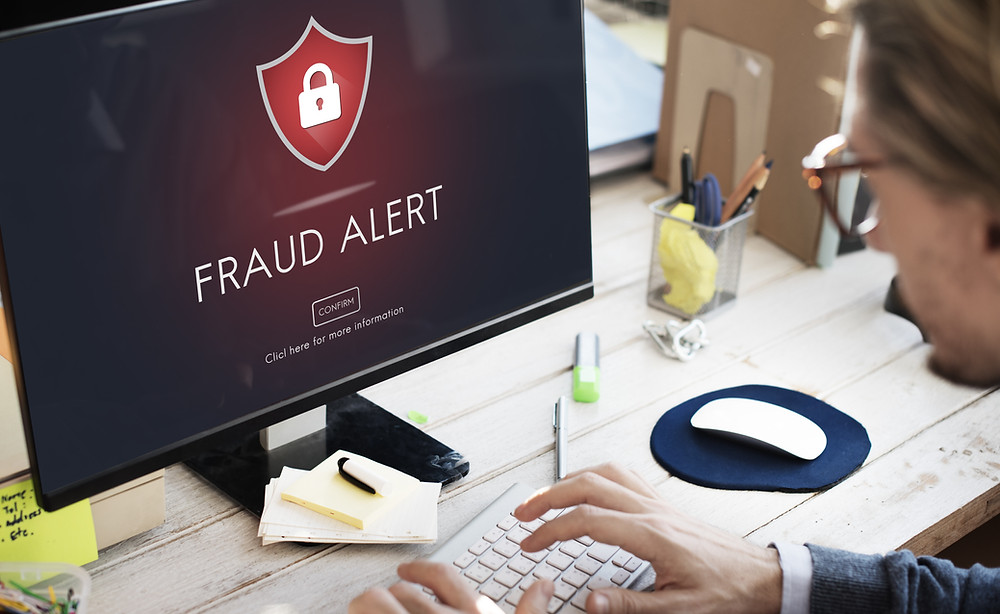 Fraud Alert type on computer screen with man typing.