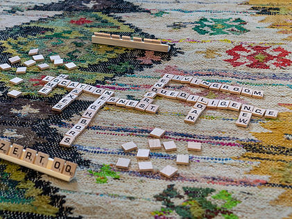 colorfulcost plus world market flat woven rug. Cream background with mustard yellow, apple green, black, pink, navy blue, red, blue and emerald green. Scrable game.